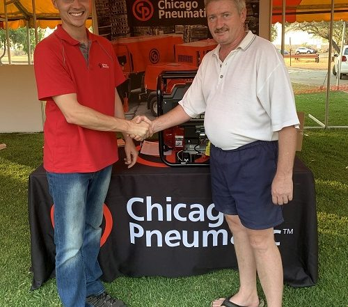 From left: Eben van der Vyver awards the prize to winner Juan Fourie at MTE's Amandelbult expo. Image credit: Chicago Pneumatic