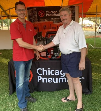 From left: Eben van der Vyver awards the prize to winner Juan Fourie at MTE's Amandelbult expo. Image credit: Chicago Pneumatic